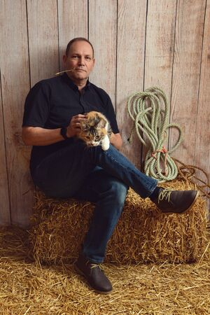 man playing with cat in a barn Imagens