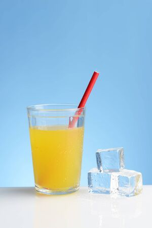 glass of cold orange juice with straw