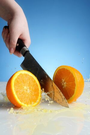 orange cut by knife with splash
