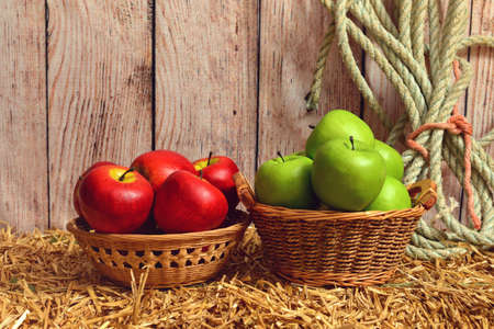 closeup red and green apples in baskets on hay bale Stock Photo