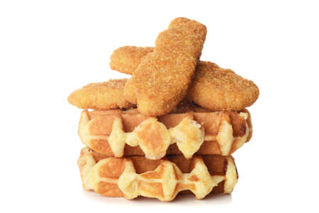 pile of belgian waffles and chicken tenders on white