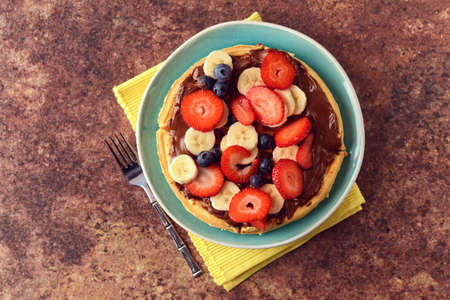 High angle view fruit waffle with chocolate spread and a fork