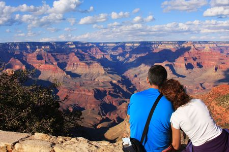 gigantic: Young Couple Sitting on cliff watching tp the Grand Canyon Stock Photo