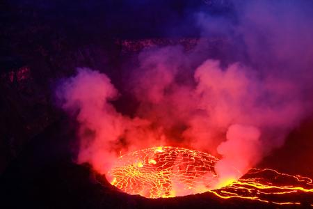 Lawa i para w kraterze wulkanu Nyiragongo w Parku Narodowym Virunga w Demokratycznej Republice Konga w Afryce. Zdjęcie zrobione o zmierzchu z unoszącym się niebieskim dymem. Zdjęcie Seryjne