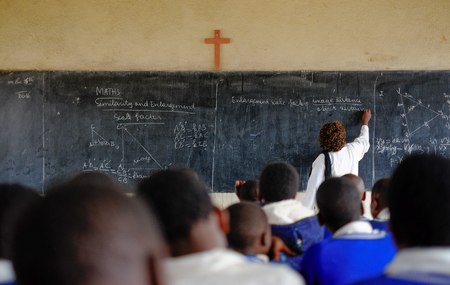 Kibuye/Rwanda - 08/26/2016: Teacher and pupils at mathematics lesson in a classroom in a school in Africa. A blackboard and cross can be seen in the background.