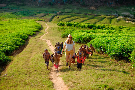 Kibuye/Rwanda - 08/25/2016: Caucasian tourist holding hands with African children walking up a hill in a tea plantation on a dusty path