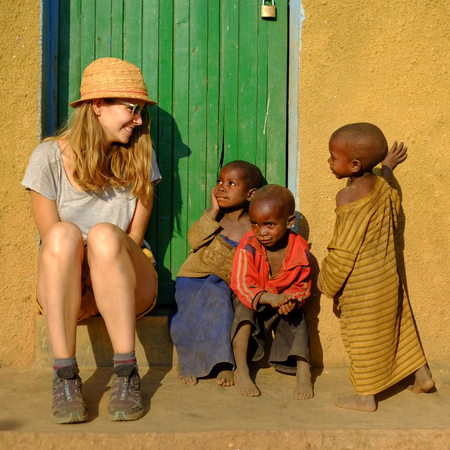 KibuyeRwanda - 08252016: Caucasian tourist with a group of African pygmy tribe children smiling and having fun in ethnic village in front of green door.