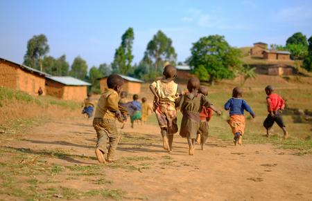 Kibuye/Rwanda - 08/25/2016: Group of african pygmy tribe children running and having fun in ethnic village on a dusty road