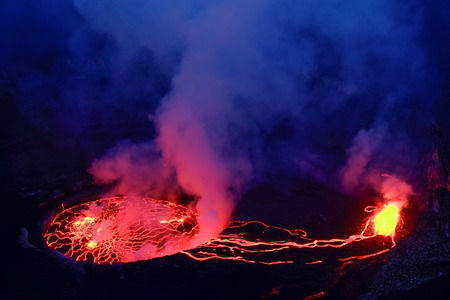 Lava and steam in crater of Nyiragongo volcano in Virunga National Park in Democratic Republic of Congo, Africa. Picture taken during dusk with blue coloured smoke rising up.