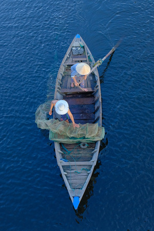 Top view of a traditional boat with local Vietnamese fishermen paddling through Hoi An, Vietnam.