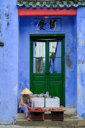 Hoi An  Vietnam, 12112017: Local Vietnamese woman sitting in front of a traditional house entrance with blue walls and selling souvenirs in Hoi An, Vietnam.