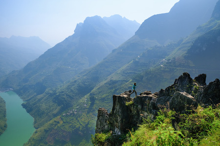 Backpacker jumping on an outcrop overlooking a valley and karst mountains in the North Vietnamese region of Ha Giang / Dong Van