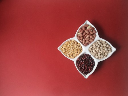 peas, beans, chickpeas and peanuts in a bowl leaf on a red background Standard-Bild