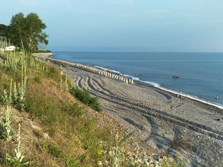 The wild seaside beach is dotted with zigzags of car wheels. Huge concrete breakwaters lie in rows on the shore. the coastal slope is covered with grass and flowers, in the background trees, outlines of buildings, cloudless azure sky, the horizon line. illegible silhouettes and figures of resting and sunbathing, floating characters are depicted. tourism, travel, Hiking, tent. there is a copy space for the text. landscape, seascape.