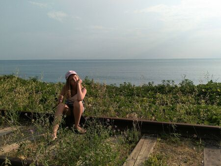 Chemitokvadzhe, Russia-June 23, 2019: a teenage girl is sitting on the rails of the old railway track in the background of the Black sea. Golden hour. 에디토리얼