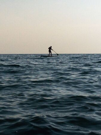 a small black silhouette of a swimmer on a sub Board with an oar on a background of light gray sky and Indigo water. small waves on the surface of the sea, glare, soft diffused light of the setting sun 写真素材