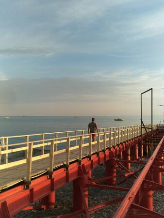 Sochi, Russia-June 20, 2019: a man in red shorts and a gray t-shirt is on a wooden flooring to the sea. Right red metal bridge. boats and boats floating on the ocean.