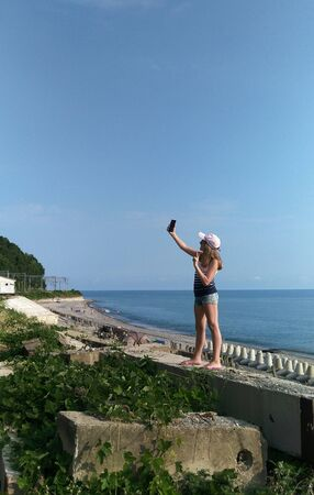 Chemitokvadzhe, Russia-June 23, 2019: teen girl selfie and a gesture of victory against the Black sea and the beach with the tips of the breakwaters