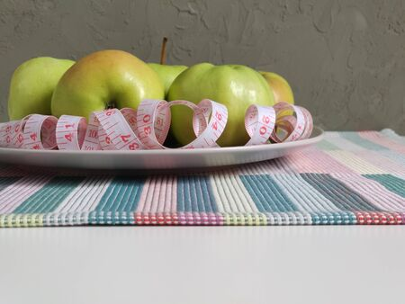 Green apples on a flat round plate with a measuring tape serpentine. white double-sided tape measure with inches and centimeters. Composition on a colored striped napkin. side view 写真素材