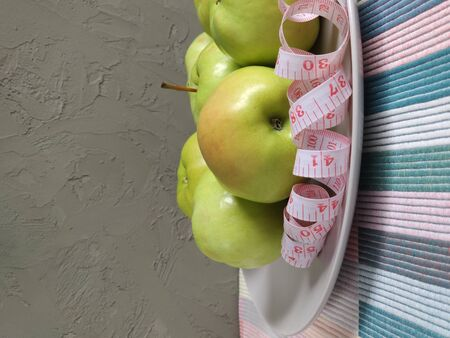 A fragment of a dish with green apples and a serpentine measuring tape around. White double-sided tape measure with inches and centimeters. Composition on a colored striped napkin. side view 写真素材
