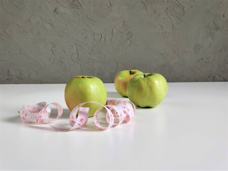 Green Apple with centimeter tape, three green apples against a gray wall, double measuring tape, serpentine with inches and centimeters bilateral