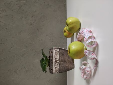 A green Apple with a centimeter ribbon and a plant in a ceramic pots with elephants, three green apples on a gray wall background, a double measuring tape, a serpentine with inches and centimeters bil