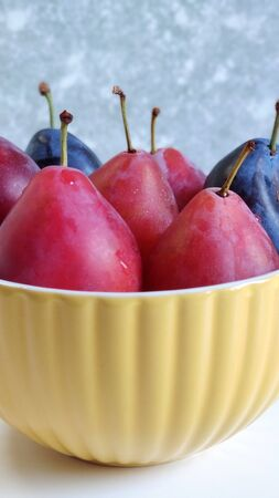 Macrophoto, a fragment of a yellow ceramic bowl with red and blue ripe plums on a white table against a blurred gray wall. Side view, flat layout, food photography.
