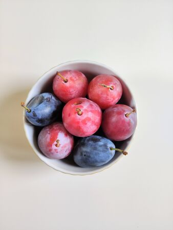 five red and two blue ripe plums in a round bowl. Top view, flat layout, food photography.