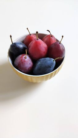 A plate of plums. Ripe red and blue plum fruit. Upper side view, foodfuture.
