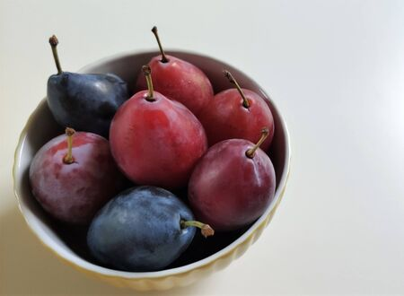 Macrophoto bowls with plums. Ripe red and blue plum fruit. Top view, flat layout, food photography.