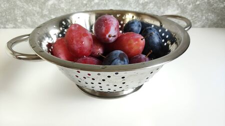 Steel colander with blue and red ripe plums. Fruit and dishes water drops. The pan stands on a white surface against a gray wall. Macrophoto, food photos.