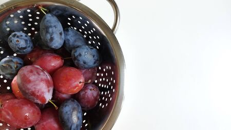 A fragment of a metal colander with Red and blue plums on a white background. Water droplets and holes in the metal. Macrophoto, Food photo, flat layout, top view. copy space for text. The subject is on the right.