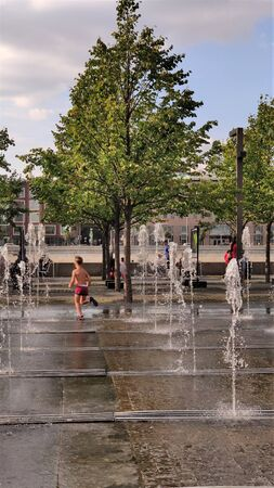 Summer in the city, swimming in the fountain, Sunny day, summer or early autumn, warm September. Walking and entertainment in an urban environment, outdoor recreation.