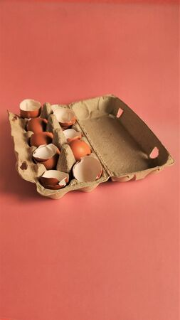 Eggshell halves in recycled cardboard packaging on a pink background. Broken eggs in a craft box, coral-colored surface. Empty shells in cardboard boxes. Processing of food waste, ecology, reuse of natural resources, preservation of the environment