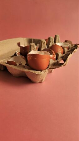 Eggshell halves in recycled cardboard packaging on a pink background. Broken eggs in a craft box, coral-colored surface. Empty shells in cardboard boxes. Processing of food waste, ecology, reuse of natural resources, preservation of the environment. Side view. Imagens