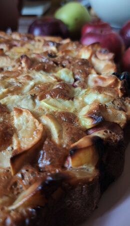 Close-up, a Fragment of Apple pie with a Golden crust. In the background, red and green apples, fragments of kitchen utensils. Front side view. Autumn harvest.