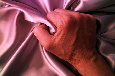 grabing: Man grabing satin sheet on the bed.