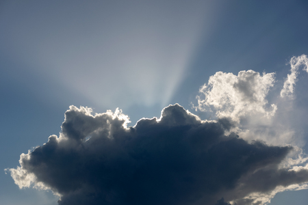 blue sky with white clouds in the suns rays in summer
