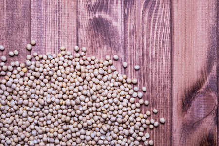 Soybeans scattered on a wooden table. Close-up soy beans