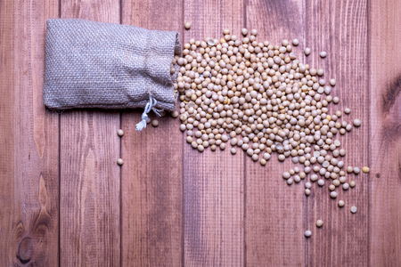 Soybeans fall out of an open canvas bag on a wooden table. Soy beans Background Stockfoto