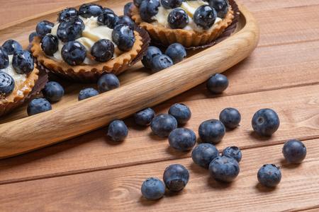 Drei Heidelbeer-Törtchen auf einer Holzplatte auf dem Tisch, Heidelbeer-Gebackene Muscheln, Obst-Cupcake mit Blaubeere.