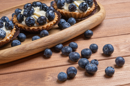 three bilberry tartlet on a wooden plate on the table, bilberry baked shells, fruit cupcake with blueberry.