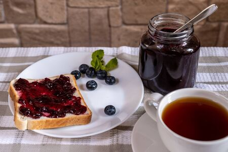 The toast with blueberry jam and a can with huckleberry jam on a light background.
