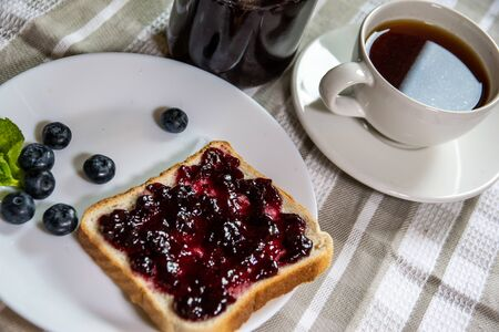 The Toast with blueberry jam and a can with huckleberry jam on a light background Banque d'images