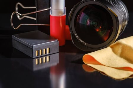 Photo accessories on a dark table. lens, battery  and cleaning brush with a microfiber napkin. Banque d'images - 135444629