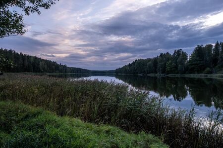 Dramatic cloudy sky over a small forest lake at sunset. Landscape scene. 스톡 콘텐츠