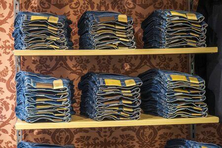 Stack of folded blue jeans pants on a shelf in a store.  Blue denim Stock fotó