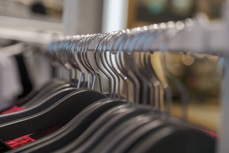 hangers with clothes in the store during the sale. Fashion clothes hanging on clothing rack.