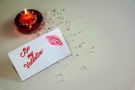 burning candle and Be My Valentine white message card with lips imprint.