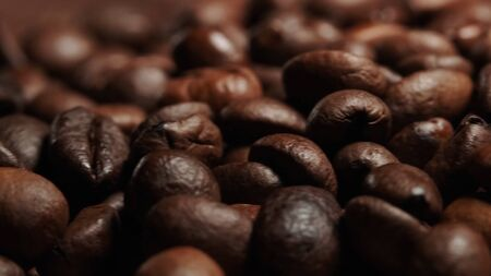Closeup of Roasted brown coffee beans lye on the table, front view. 스톡 콘텐츠